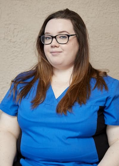 Jess wearing glasses and her Genesis Chiropractic Clinic uniform
