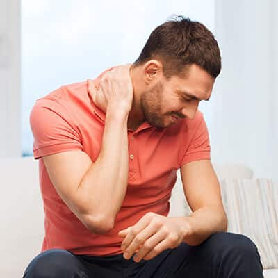 Man holding his neck because he is experience pain that Dr. Fish can help with - contact us