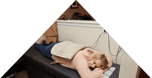 Triangle shape with a woman laying on a rehab table. She has a heat pack on her back to help circulation.